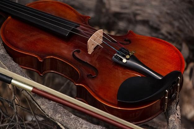 El violín y el arco de madera colocados en un tablero de madera, una luz borrosa alrededor