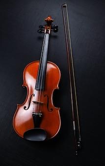 El violín y el arco de madera puestos en la pared de lona negra