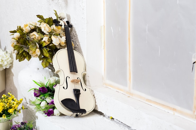 Violín blanco con flores y sala blanca