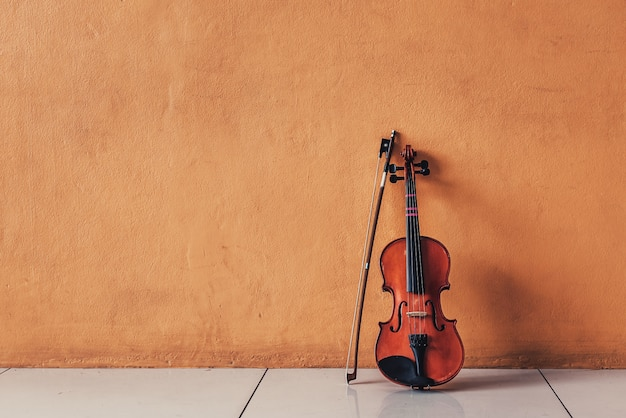 Violín clásico antiguo puesto en paredes de cemento naranja