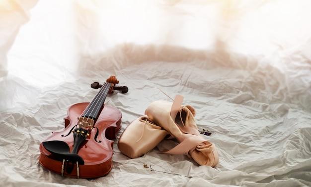 El violín de madera puesto al lado de zapatillas de ballet, en el fondo, tono de luz cálido