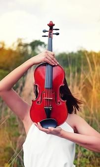El violín de madera sostenía las manos de una mujer, cerró la cara, mostró detalles del instrumento de cuerda, tono vintage y artístico, luz borrosa alrededor