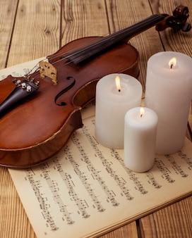 El violín y las notas cierran encima de mentir en la tabla de madera.