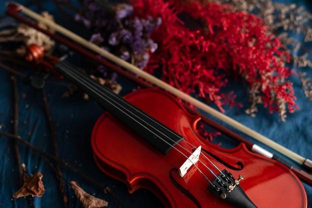 Violín puesto al lado de flor borrosa sobre fondo de superficie grunge, vintage y tono de arte