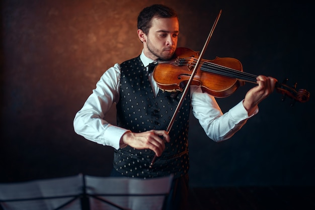 Violinista masculino tocando música clásica en violín