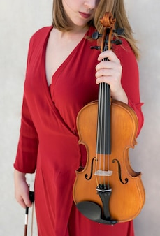 Violinista posando mientras sostiene el violín