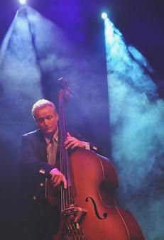 El violonchelista de jazz toca el violonchelo bajo las luces del escenario