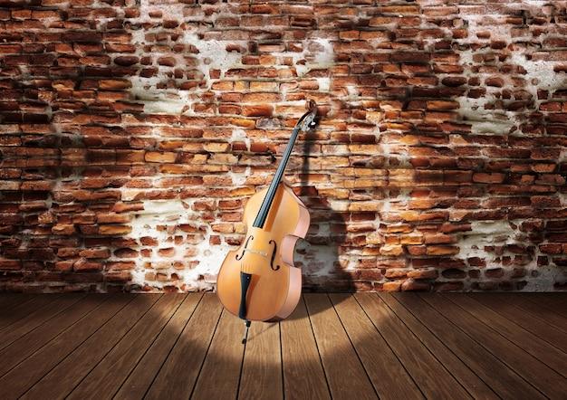 Violonchelo en el escenario apoyado contra la pared de ladrillos rústicos