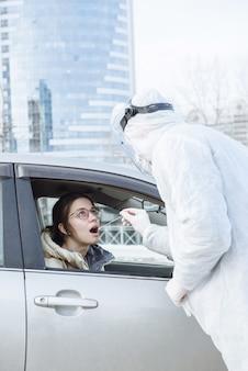 Un virólogo o médico con ropa protectora de materiales peligrosos ppe toma una muestra de una prueba de pcr con un hisopo de algodón