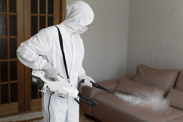 Virólogo en traje protector de materiales peligrosos realiza desinfecciones de superficies