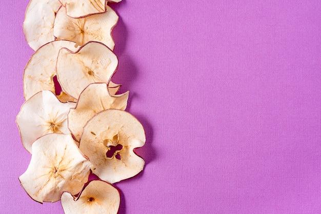 Virutas secas de la manzana sobre púrpura con el espacio de la copia.