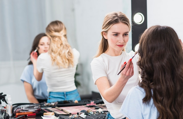 Visagiste creando maquillaje profesional mujer en estudio.