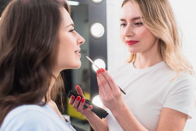 Visagiste haciendo maquillaje de labios al cliente.