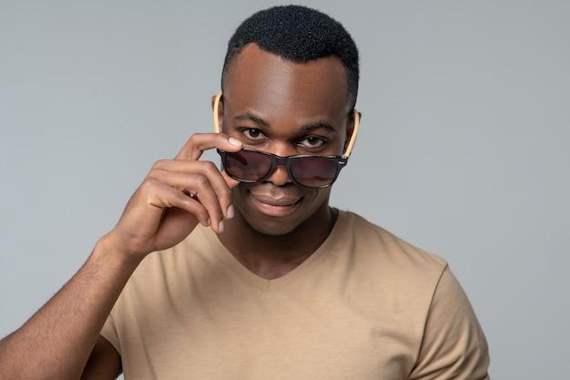 Visión. feliz joven afroamericano en gafas de sol de pie mirando de buen humor en el estudio