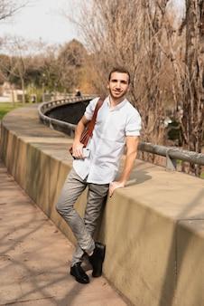 Visión a largo plazo del hombre que presenta afuera en una camisa blanca