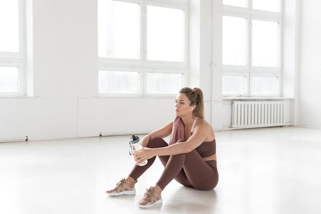 Visión a largo plazo de la mujer sentada en gimnasio