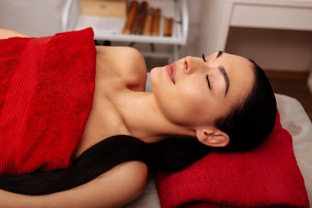 Visita al centro de spa. mujer atractiva de pelo oscuro pacífica acostada en la cama de masaje con el cuerpo desnudo y cubierto con una toalla