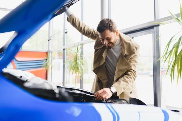 Visita al concesionario de automóviles. hombre guapo con barba está acariciando su nuevo coche y sonriendo