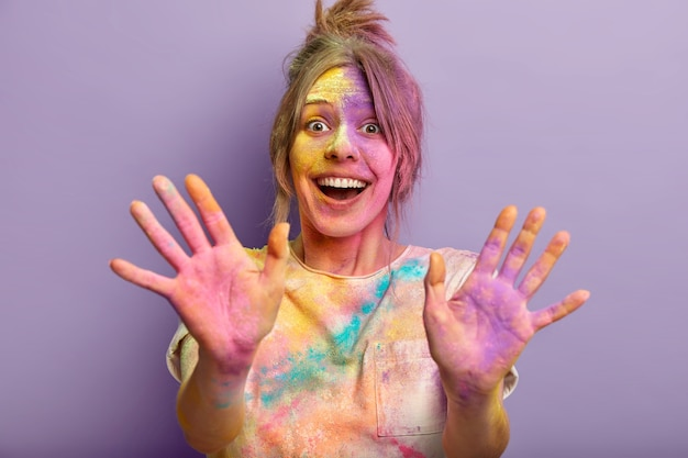 Visita el festival de colores de holi. la mujer sonriente feliz tiene salpicaduras de colores sobre sí misma, sucia con polvo, demuestra palmas pintadas multicolores, aisladas sobre la pared violeta. concepto de celebración