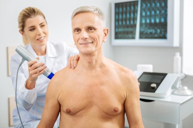 Visita a un hospital. encantado de hombre guapo agradable sonriendo y mirando frente a él mientras es examinado