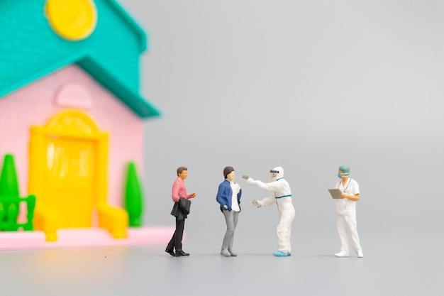 Visita médica de ppe de personas en miniatura para verificar el coronavirus en el hogar, concepto de atención médica
