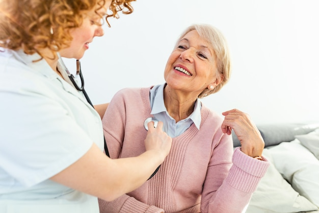 Visitante de salud y una mujer mayor durante la visita al hogar