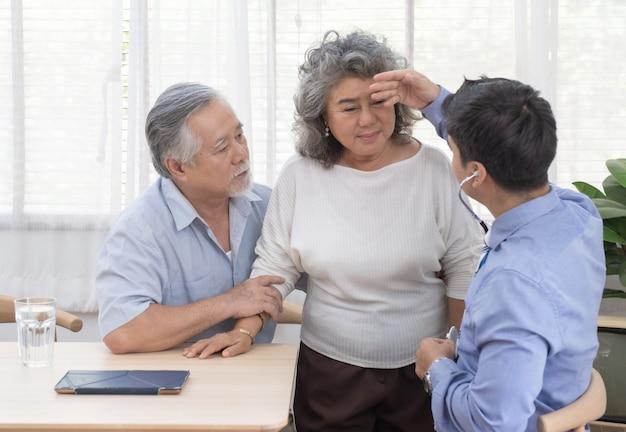 Visitante de salud y mujer mayor durante la visita al hogar.