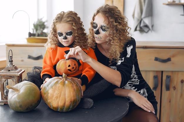Víspera de todos los santos. madre e hija en disfraz de halloween de estilo mexicano. familia en casa con calabazas.