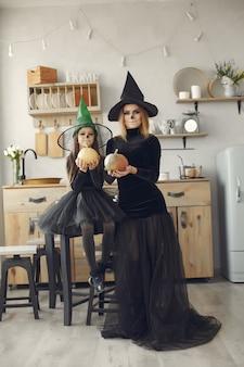 Víspera de todos los santos. madre e hija disfrazadas de halloween. familia en casa.