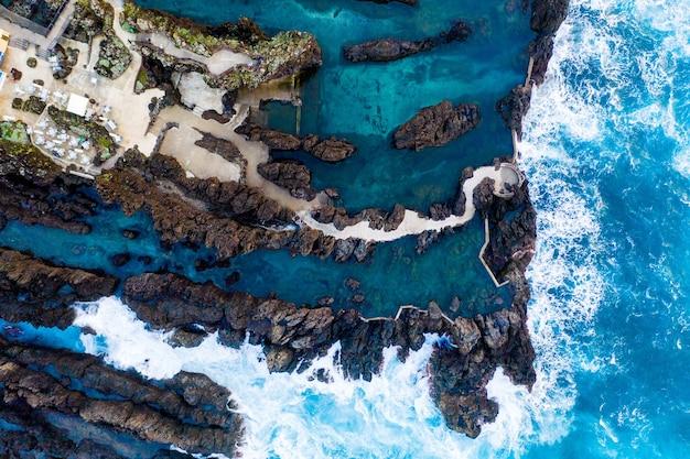 Vista aérea de los acantilados de la isla oceánica con enormes olas blancas y agua azul cristalina