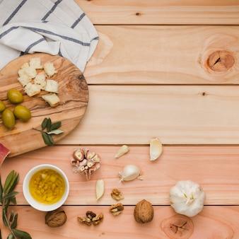 Una vista aérea de las aceitunas; un pan; nueces y aceites de oliva infundidos en mesa de madera.