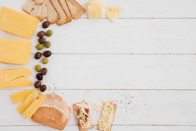 Una vista aérea de las aceitunas; rebanada de queso y pan en mesa de madera blanca