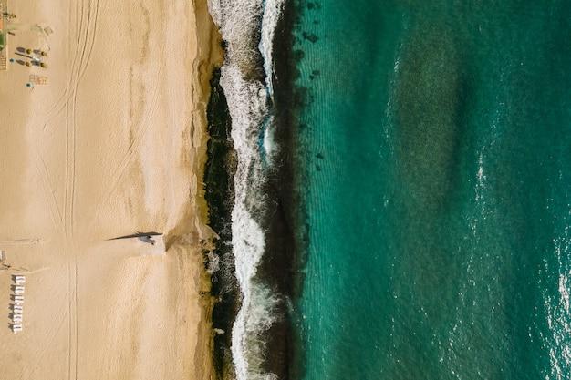 Vista aérea de arena que se encuentra con el agua de mar y las olas
