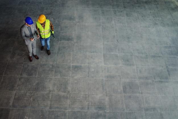 Vista aérea del arquitecto y trabajador de la construcción de pie en el sitio y discutiendo sobre el proyecto