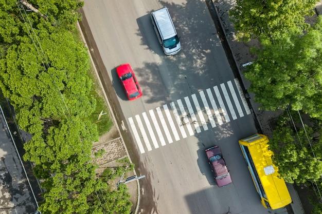 Vista aérea de arriba hacia abajo de una calle concurrida con tráfico de automóviles en movimiento y paso de peatones de la carretera de cebra.