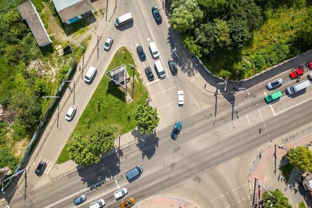 Vista aérea de arriba hacia abajo de la concurrida intersección de calles con tráfico de automóviles en movimiento.