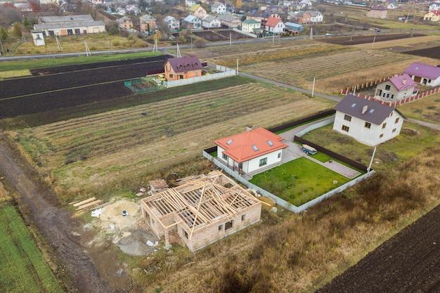 Vista aérea de arriba a abajo de dos casas privadas, una en construcción con marco de madera para techos y otra terminada con techo de tejas rojas.