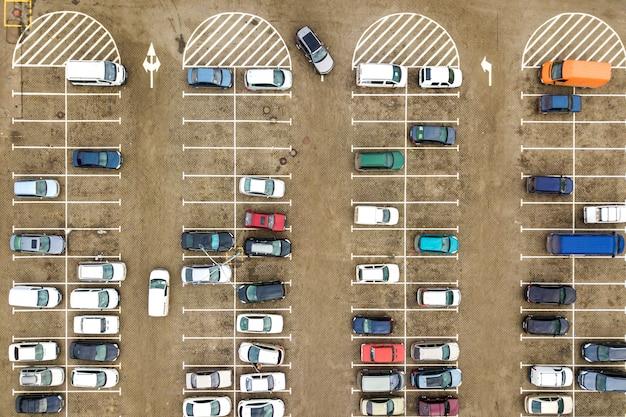 Vista aérea de arriba hacia abajo de muchos automóviles en un estacionamiento del supermercado o en el mercado de concesionarios de automóviles en venta.