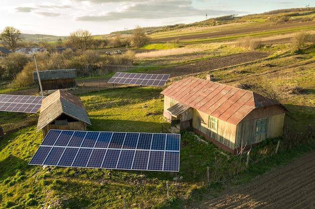 Vista aérea de arriba hacia abajo de paneles solares en el patio de la aldea rural verde.