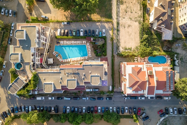 Vista aérea de arriba hacia abajo de los techos de los hoteles, calles con autos estacionados y piscinas con agua azul en la ciudad turística cerca del mar.