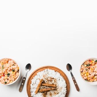 Vista aérea de arroz frito y de vapor chino con palitos de canela en superficie blanca