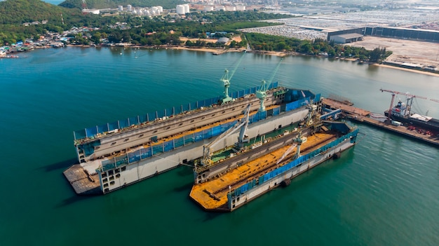 Vista aérea del astillero tiene grúa máquina y barco de contenedores en el océano negro