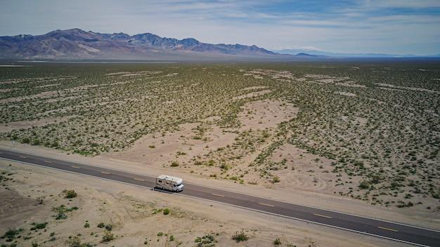 Vista aérea de una autocaravana conduciendo por una carretera en el desierto de california, estados unidos