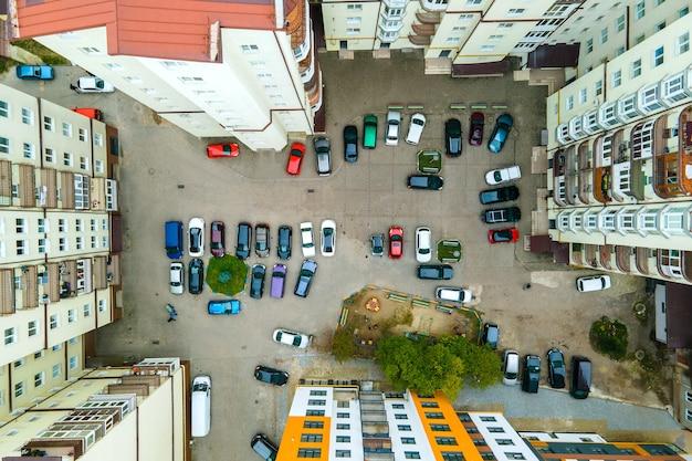 Vista aérea de automóviles estacionados en el estacionamiento entre edificios de apartamentos altos