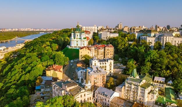 Vista aérea de aviones no tripulados de la iglesia de san andrés y la calle andreevska desde arriba, paisaje urbano del distrito de podol al atardecer, horizonte de la ciudad de kiev (kiev), ucrania