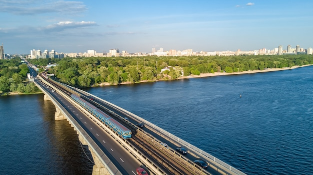 Vista aérea de aviones no tripulados del puente ferroviario de metro con tren y río dnieper desde arriba, horizonte de la ciudad de kiev, ucrania