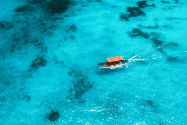 Vista aérea del barco de pesca en agua azul transparente en un día soleado en verano