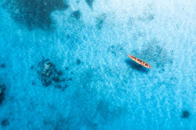 Vista aérea del barco de pesca en agua azul transparente