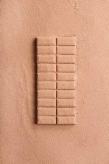 Vista aérea de una barra de chocolate espolvoreada con cacao en polvo.