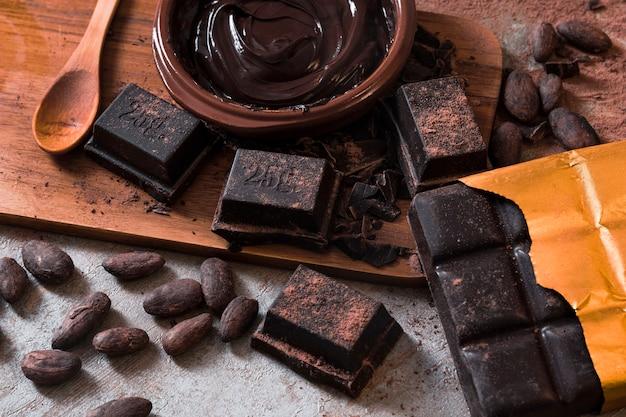 Vista aérea de barra de chocolate y piezas con granos de cacao